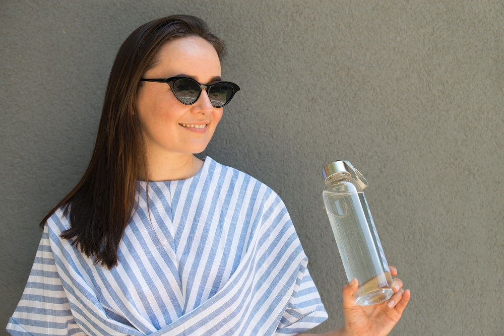 Woman Is Holding Glass Bottle With Clear Water